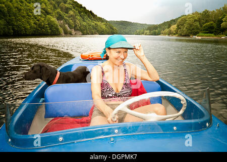 Woman driving an electric boat, a dog standing at the back - Stock Photo