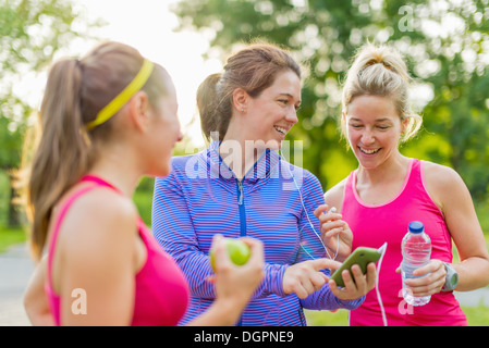 Group of happy active girls preparing for a run in nature by choosing music on a smart phone - Stock Photo