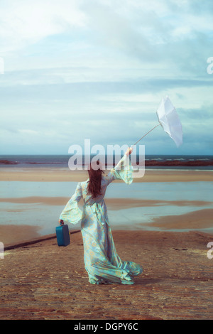 a woman in a floral dress on a slip with a suitcase, holding an upended umbrella in the wind - Stock Photo