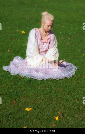 a woman in a period dress is sitting in the grass, reading a book - Stock Photo
