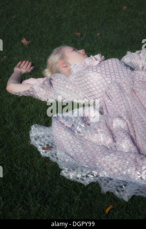 a woman in a period dress is lying in the grass - Stock Photo