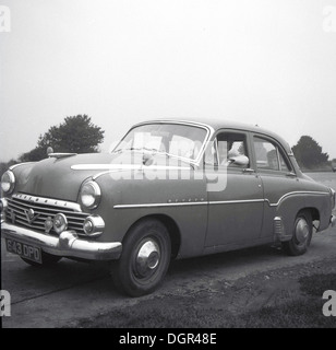 Historical picture from 1950s showing a lady sitting in the passenger seat of a vintage car. - Stock Photo