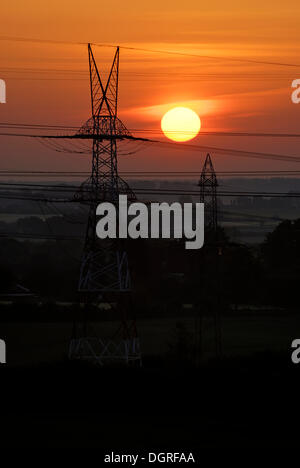 High-voltage transmission line in front of the rising sun, near Rendsburg, Schleswig-Holstein - Stock Photo