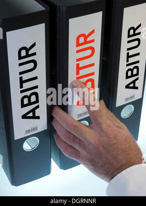 Hand reaching for a file folder labeled 'Abitur', German for 'A level' - Stock Photo