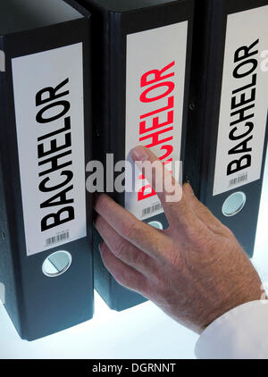 """Hand reaching for a file folder labeled """"Bachelor"""" - Stock Photo"""