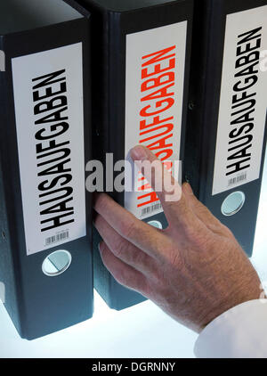 Hand reaching for a file folder labeled 'Hausaufgaben', German for 'homework' - Stock Photo