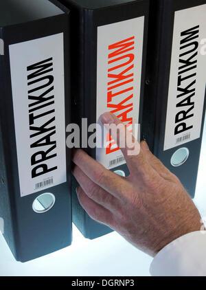 Hand reaching for a file folder labeled 'Praktikum', German for 'internship' - Stock Photo