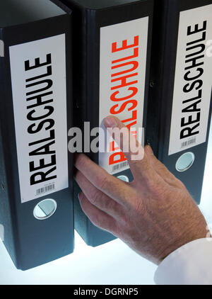 Hand reaching for a file folder labeled 'Realschule', German for 'middle school' - Stock Photo