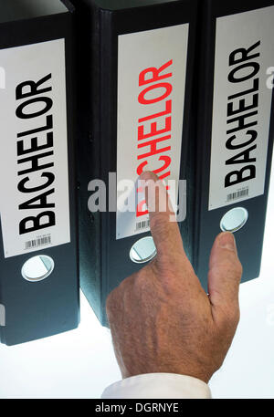 """Hand pointing to a file folder labeled """"Bachelor"""" - Stock Photo"""