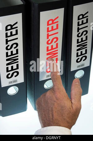 Hand pointing to a file folder labeled 'Semester' - Stock Photo