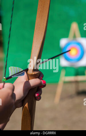 Archer aiming bow and arrow at target, Hesse