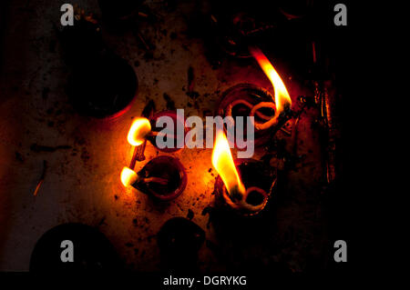 Burning oil lamps in an Indian temple - Stock Photo