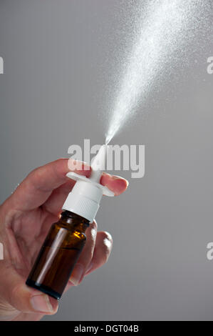 Spray from a nasal spray in a brown glass bottle - Stock Photo