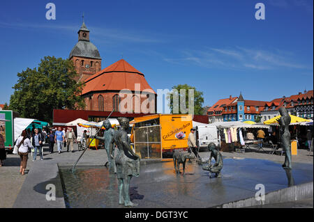 Weekly market on Marktplatz square, St.-Marien-Kirche church at the back, originally a brick building from the 13th - Stock Photo