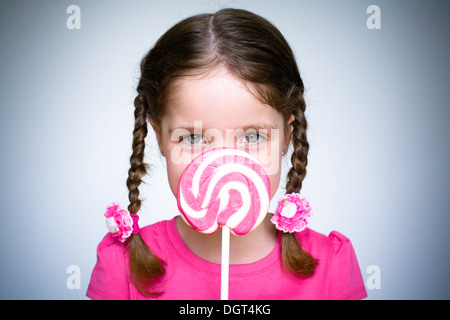 A young girl holds a large spiral lollypop whilst dressed in pink. - Stock Photo