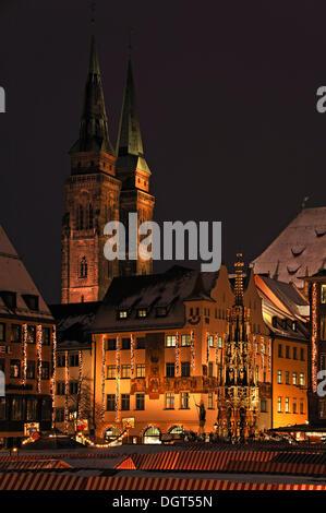 Illuminated Nuremberg Christmas market, Schoene Brunnen or Beautiful Fountain and St. Sebald Church at the rear, - Stock Photo