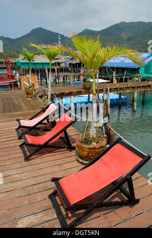 Red deck chairs on the pier in the Bang Bao bay, Koh Chang Island, National Park Mu Ko Chang, Trat, Gulf of Thailand, - Stock Photo