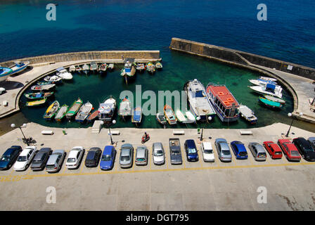 Parked cars and fishing boats in the harbour area, Marsalforn Bay, Marsalforn, Island of Gozo, Malta, Mediterranean - Stock Photo