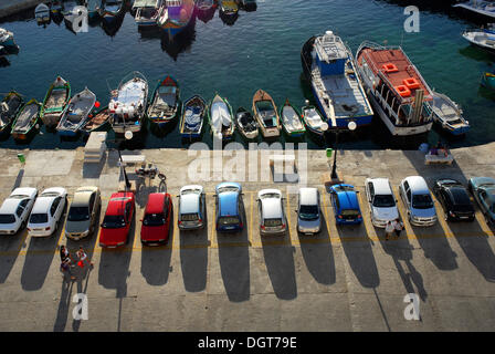 Parked cars and fishing boats in the harbour, Bay of Marsalforn, Marsalforn, Gozo Island, Malta, Mediterranean Sea, - Stock Photo