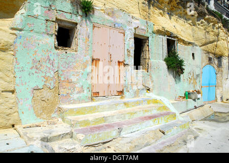 Steps leading up to a room inside the rocks, pastel colours in the harbour area, Marsalforn Bay, Marsalforn, Island - Stock Photo