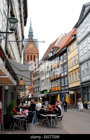 Cafe and bar in the old town, half-timbered houses in the Kramerstrasse street, in the back the Marktkirche church, - Stock Photo
