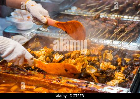 Food preperation at a night market in Myeong-dong, Seoul, South Korea. - Stock Photo