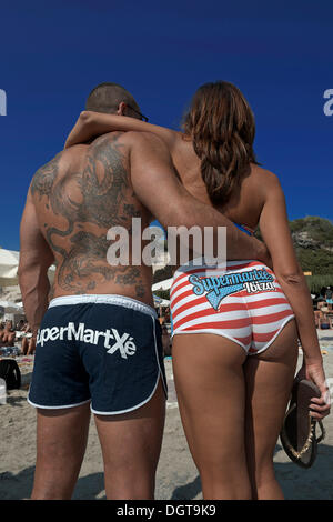 Man in swimming trunks and a woman in a bikini, members of a promotional team from one of the big clubs advertising - Stock Photo