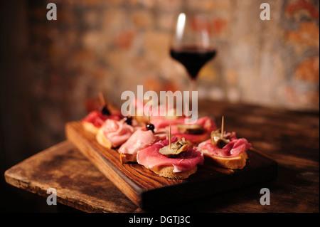 Cured meats Cicchetti appetizers at La Mascareta Restaurant, Venice, Italy. - Stock Photo