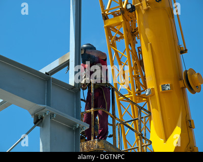 welder with protective mask welding metal construction - Stock Photo
