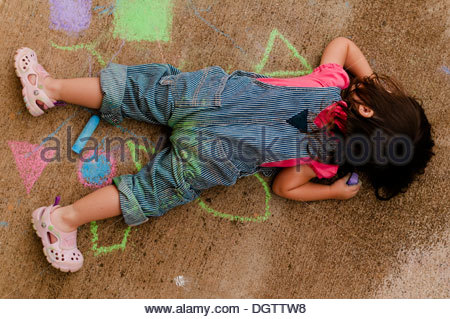 Toddler playing with chalk on the sidewalk. - Stock Photo