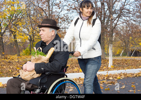 Smiling carer pushing an old man in a wheelchair stock photo image - Senior Man Carrying Groceries In Cloth Bags Winnipeg
