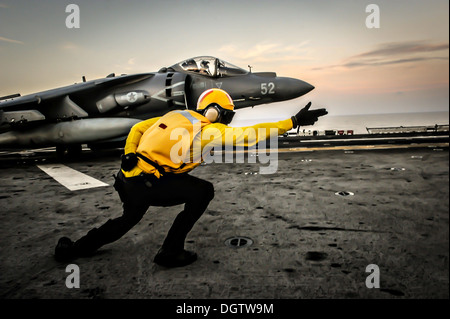 A US Sailor directs a US Marine Corps AV-8B Harrier II fighter aircraft to take off from the flight deck aboard - Stock Photo