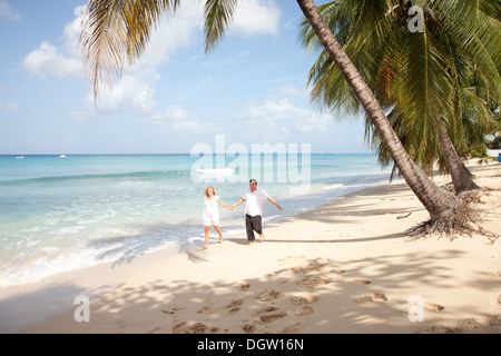 couple running towards camera on the beach in Barbados - Stock Photo