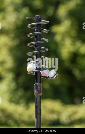 Golf Balls on a metal spiral form a queue - Stock Photo