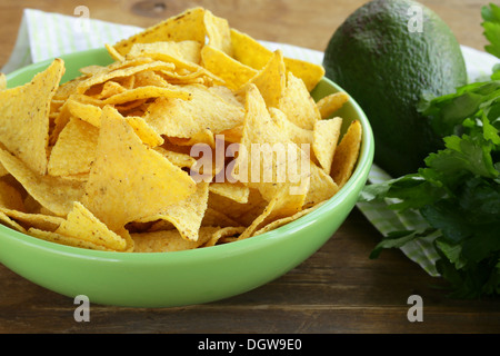 avocado on a wooden table and corn chips in the background - Stock Photo