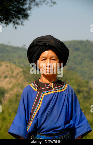 Portrait of a woman of the Ho ethnic group in traditional colourful blue dress and black turban, Phongsali or Phongsaly - Stock Photo
