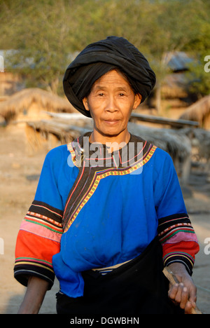 Portrait of a woman of the Lolo ethnic group in traditional colourful blue dress and black turban, village of Ban - Stock Photo