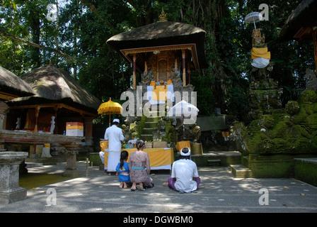 Bali Hinduism, devout family kneeling in front of shrine, Brahmin priest in white robe, Pura Griya Sakti Temple - Stock Photo