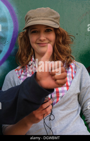 Female teenager being given the thumbs up sign - Stock Photo