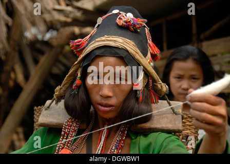 Portrait of a young woman of the Akha Eupa ethnic group concentrating on spinning cotton, wearing traditional clothes - Stock Photo