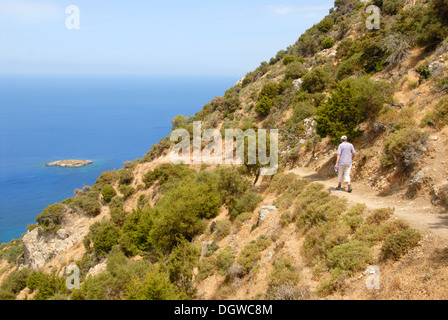 Woman hiking along a steep coastal cliff trail, looking over an island and the blue sea, descending from Moutti - Stock Photo