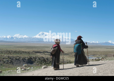 Tibetan Buddhism, two pilgrims hiking, dressed in traditional costume, behind Mt. Gurla Mandhata, pilgrimage route - Stock Photo