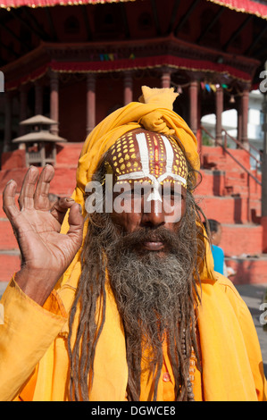 Portrait, holy man blessing with his hand, Mudra, Sadhu, brightly painted forehead, orange robe, beard, Hinduism, - Stock Photo
