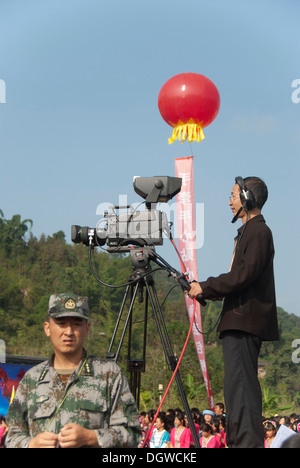 Censorship, censoring the press, a soldier guarding in front of a cameraman with a television camera, TV broadcast - Stock Photo