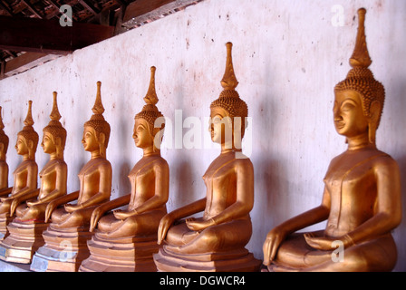Theravada Buddhism, meditation, row of bronze Buddha statues, temple, That Ing Hang Stupa, in Savannakhet, Laos, - Stock Photo