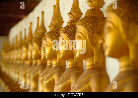 Theravada Buddhism, meditation, row of golden Buddha statues, temple, That Ing Hang Stupa, in Savannakhet, Laos, - Stock Photo