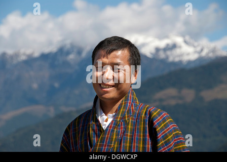 Man smiling, portrait, wearing traditional Gho dress, plaid fabric, the Himalayas, Bhutan, South Asia, Asia - Stock Photo