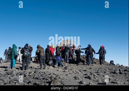 Mountaineering, mass tourism, many mountaineers at a sign on the summit of Mount Kilimanjaro, Kibo, Uhuru Peak, - Stock Photo