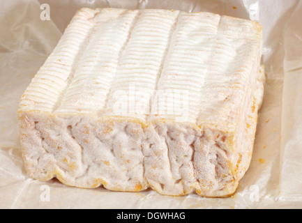 A block of Pont-l'eveque French Normandy cheese resting on its greaseproof paper wrapping - Stock Photo