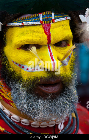 Man in a colourfully decorated costume with face paint is celebrating at the traditional Sing Sing gathering in - Stock Photo